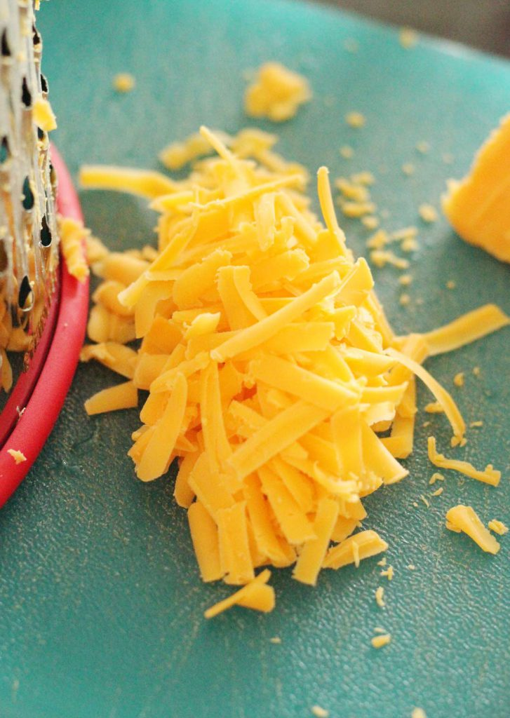I like to shred my cheese by hand. It assures that it is gluten free and that my finger muscles are worked out.  They are very conscientious about their workouts.